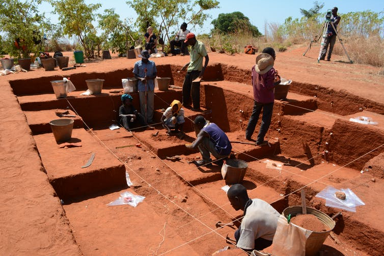 people digging in red earth at an outdoor archaeological site