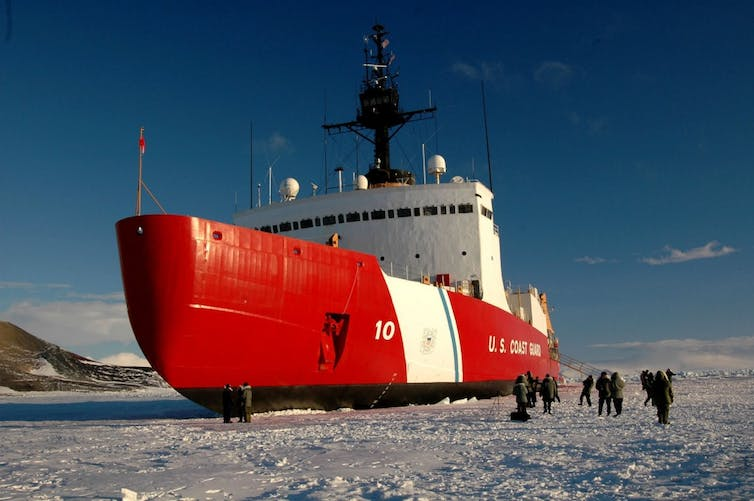 People walk on the ice beside the giant icebreaker