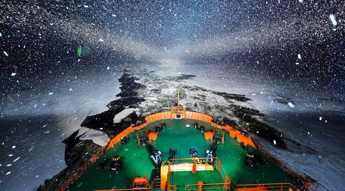 An icebreaker at night with the open channel of water through the ice behind it