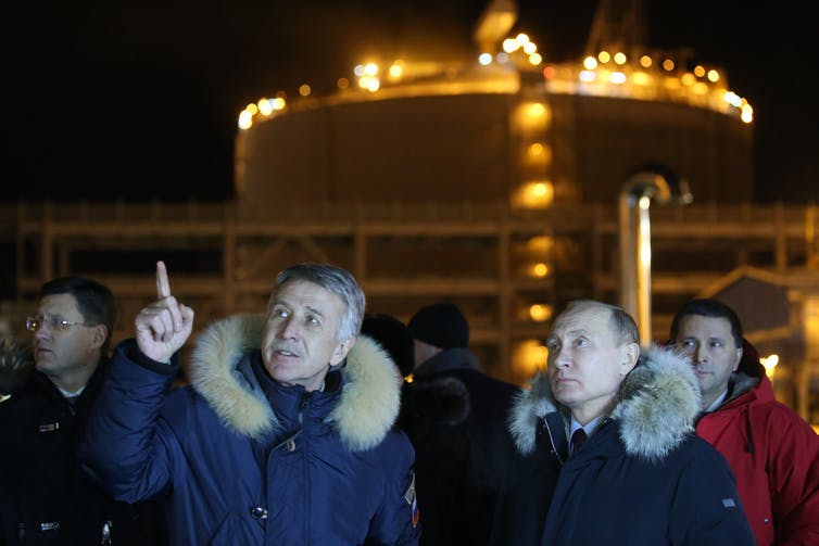 Russian President Vladimir Putin stands a man who is pointing outside the lit-up LNG plant.