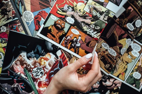 Hand flipping through comic book pages.