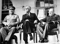 The three leaders sitting in chairs on a portico