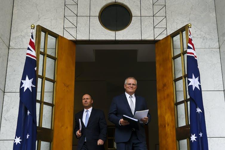 Treasurer Josh Frydenberg and Prime Minister Scott Morrison walking through a doorway.