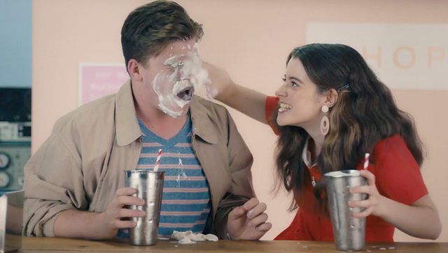 Girl smearing milkshake over boy's face