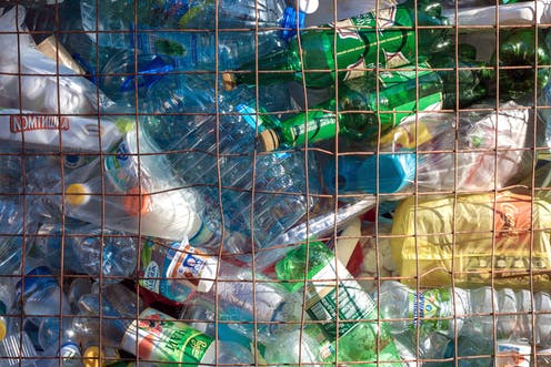 Plastic bottles are piled up behind metal fencing