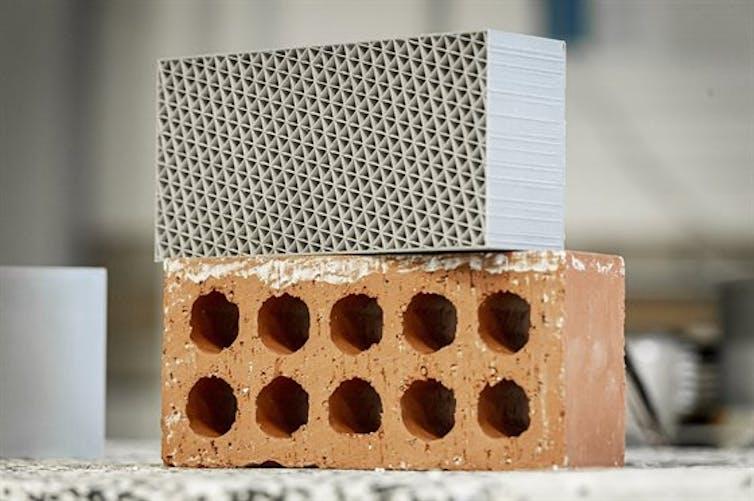 A 3D-printed plastic brick sits atop a a clay brick