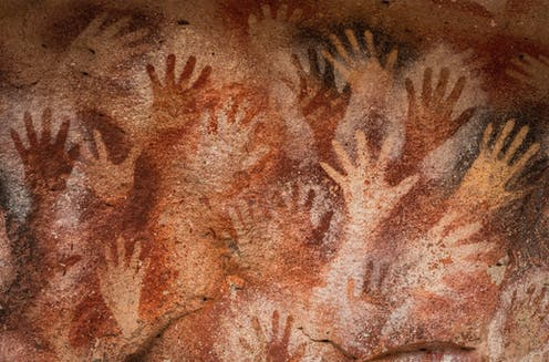 A number of hand stencils on a cave wall