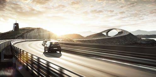 An electric car driving along an empty motorway.