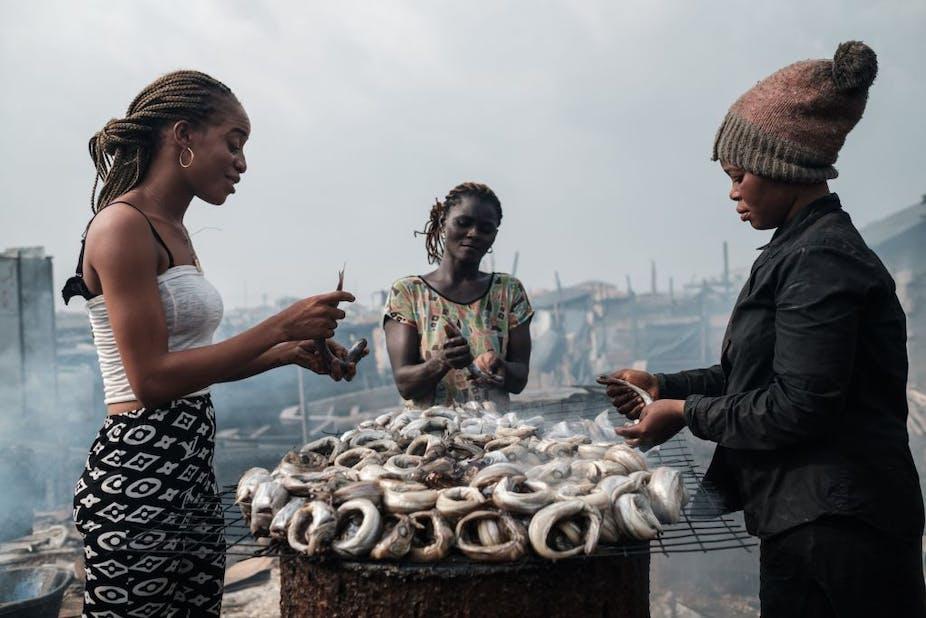 A group of women smoke fish