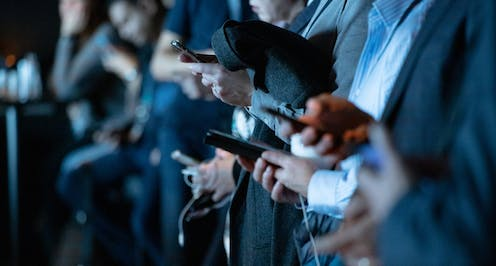 People holing their smartphones.