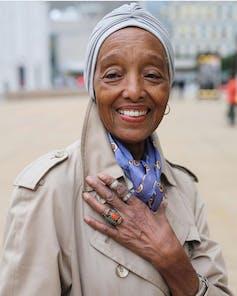 Une femme âgée portant un trench-coat, un foulard coloré et un foulard de tête