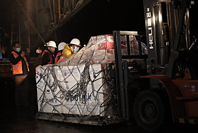 Workers in hard helmets unload a shipment of Sputnik V vaccines.