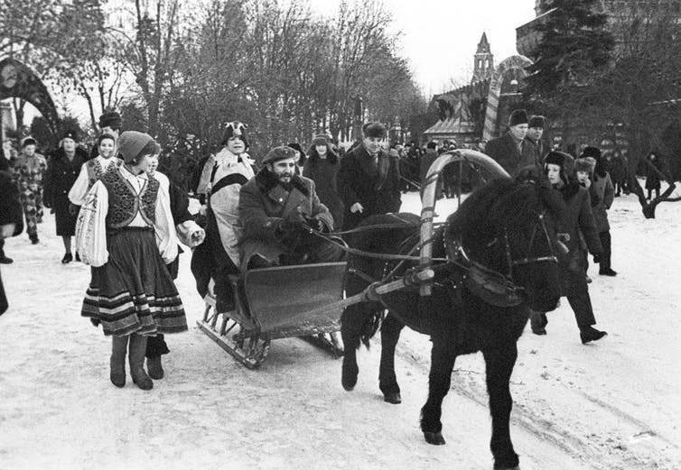 Black-and-white photo of Castro, in his traditional revolutionary beret, driving a horse-drawn sleigh in the snow, surrounded by Russians in traditional dress