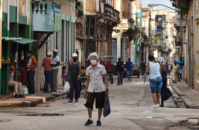 An elderly person wearing a face mask walks along a street of Havana, holding a grocery bag