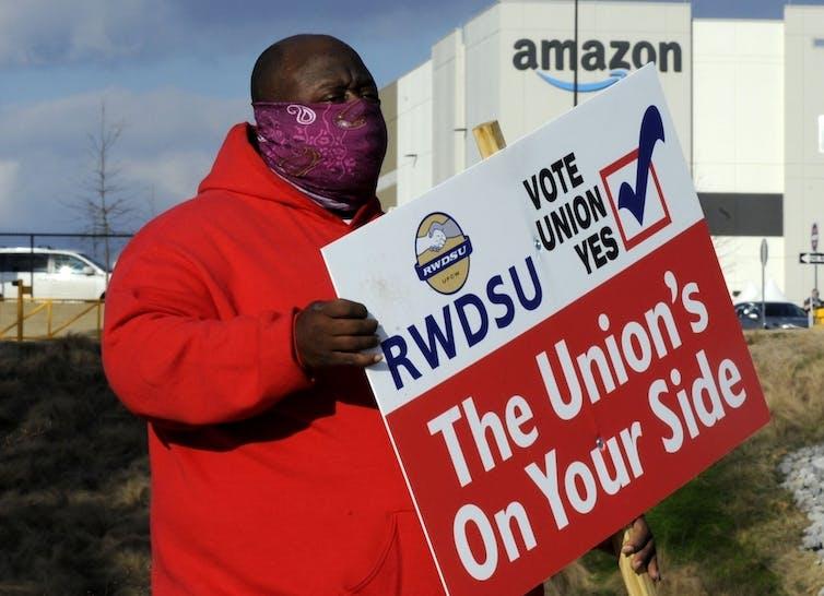 Un homme en manteau rouge tenant une pancarte pro-syndicat se trouve à l'extérieur d'une installation Amazon à Bessemer, Alabama