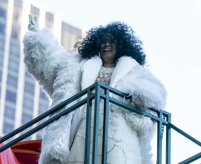 Diana Ross, wearing white fur, gloves and a silve and white dress.