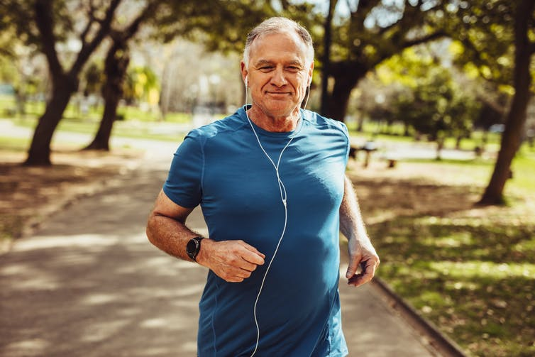 A man wearing headphones jogs in the park.