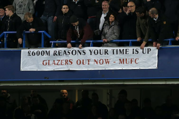 Manchester United fans unfurl a banner against the Glazer ownership of the club.
