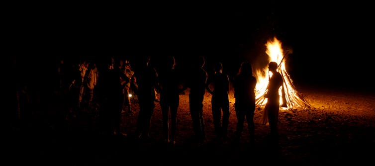 people silhouetted against bonfire at night