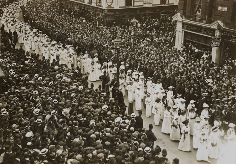 A stream of women in white between crowds of men in black.