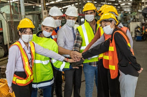 Masked workers in hard hats touch hands