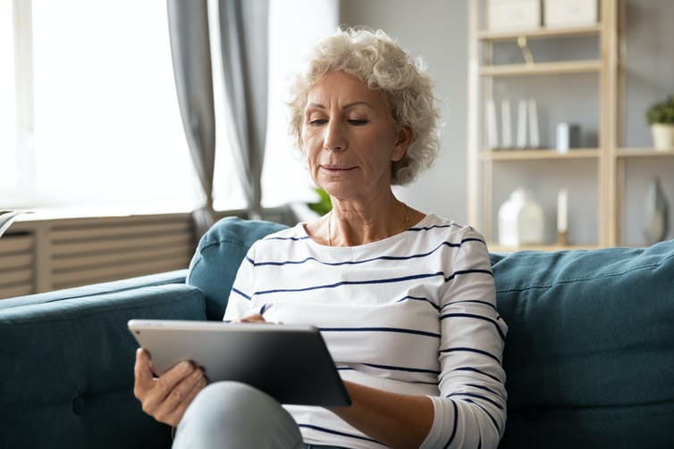 A senior woman uses an iPad on the couch.
