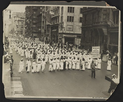 A parade of black women in white.