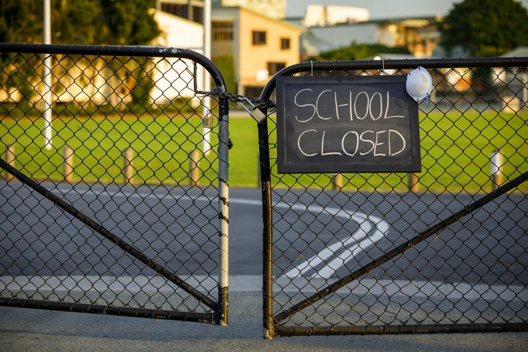 A 'school closed' sign hangs on school gates.