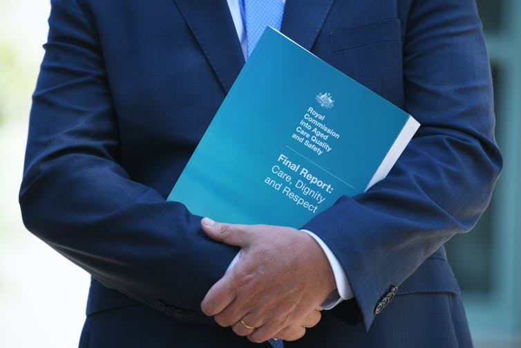 Prime Minister Scott Morrison holding a copy of the aged care royal commission report.