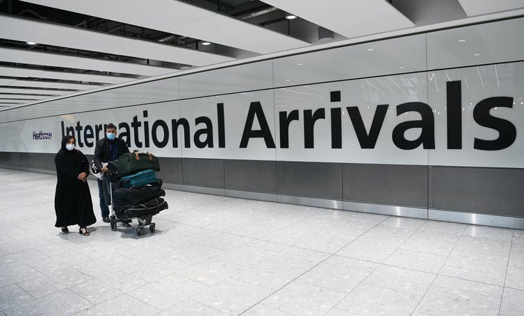 Two people walking into the arrivals terminal with luggage at Heathrow