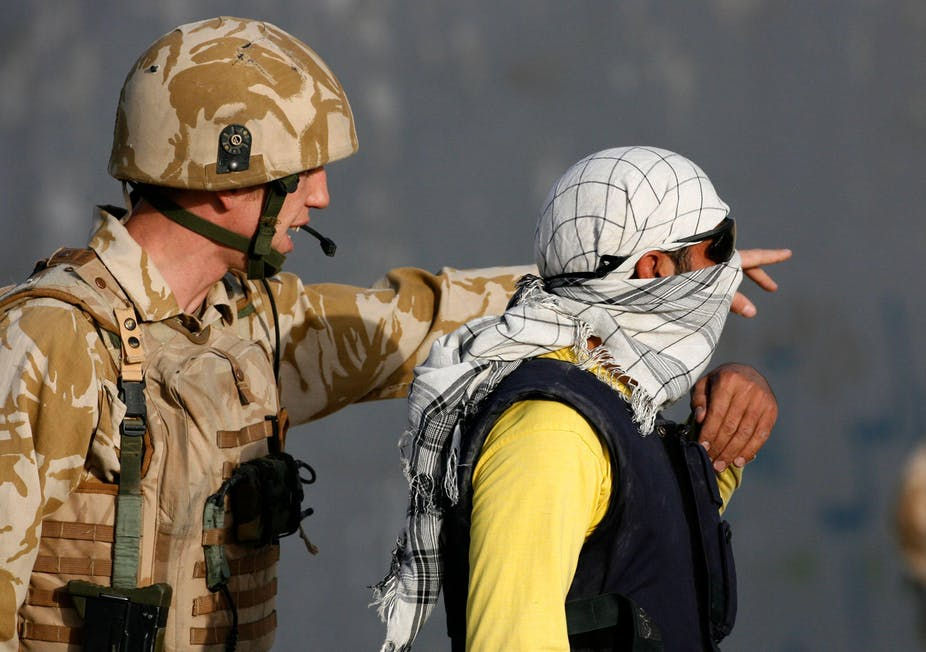 A man wearing British military uniform speaks to an Afghani man wearing sunglasses and a headscarf.