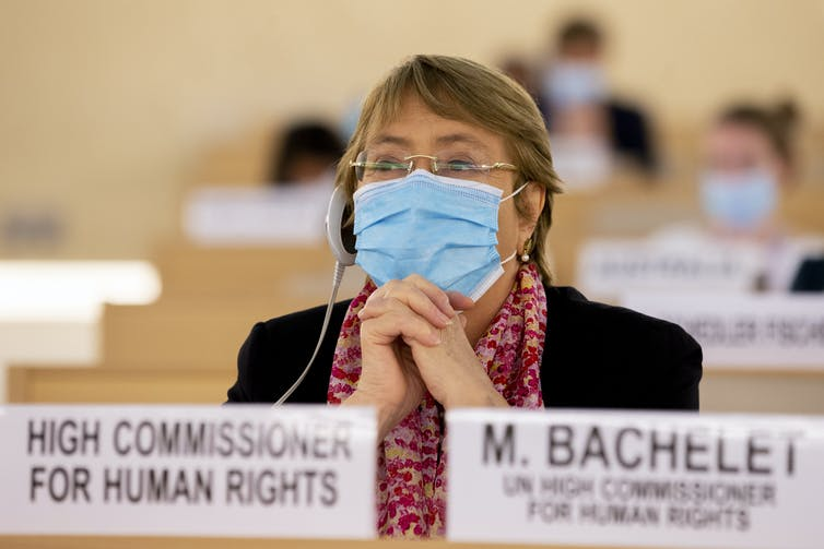 Woman wearing headphones and face mask sits listening.