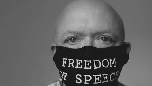 A bald man wearing a COVID mask with the words 'Freedom of Speech'.