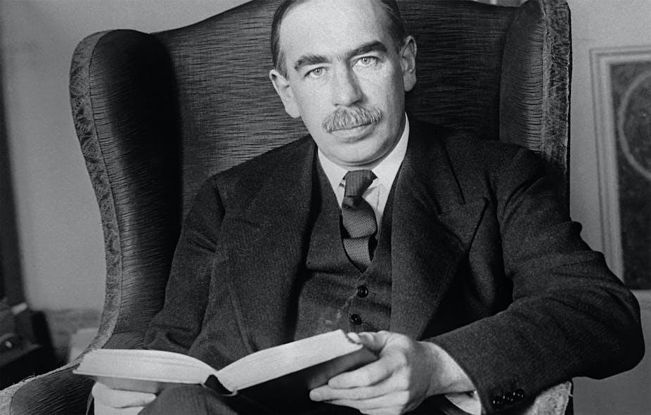John Maynard Keynes reading a book on an armchair