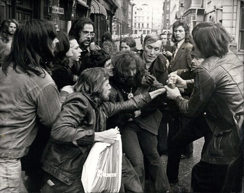 Black and white 1970s photo of a group of men in a struggle