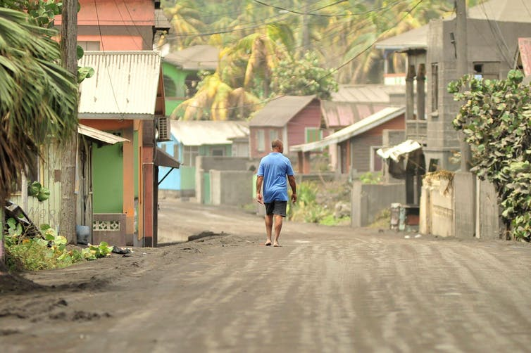 A man walks down a street after a series of eruptions from La Soufrière volcano covered the area with a thick layer of ash.
