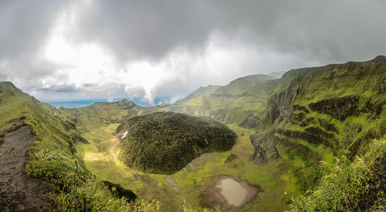 The La Soufriere volcano crater, covered in green, with clouds in the background.