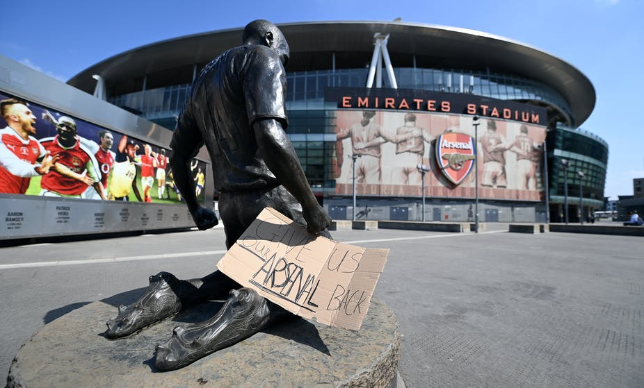 """Statue outside of Arsenal Emirates Stadiium with sign saying """"Give us our Arsenal Back"""""""