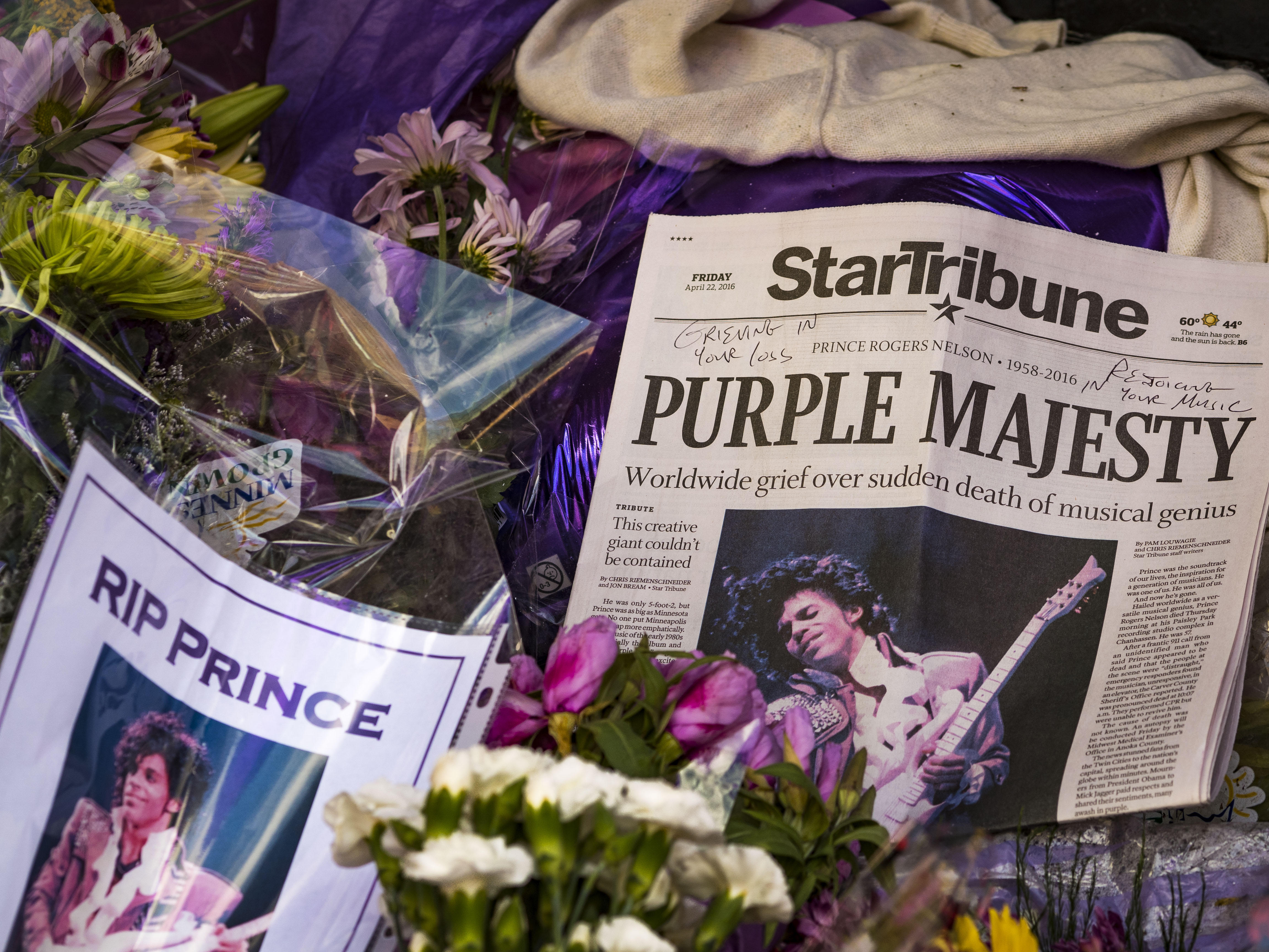 Memorial for the artist Prince with newspaper cuttings from the day of his death, flowers and a sign that says 'RIP Prince'