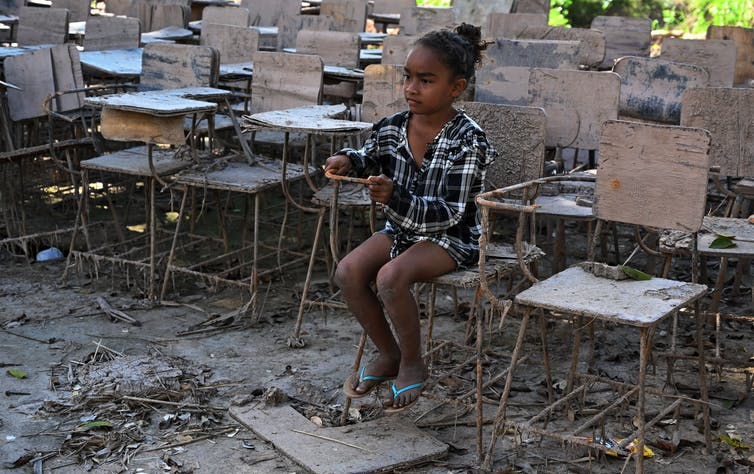 A girl sits in a muddy, destroyed school chair on muddy, messy ground