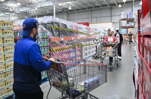 People wearing masks push their shopping carts in a Costco.
