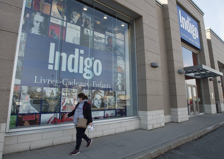 A woman in a mask walks by an Indigo store.