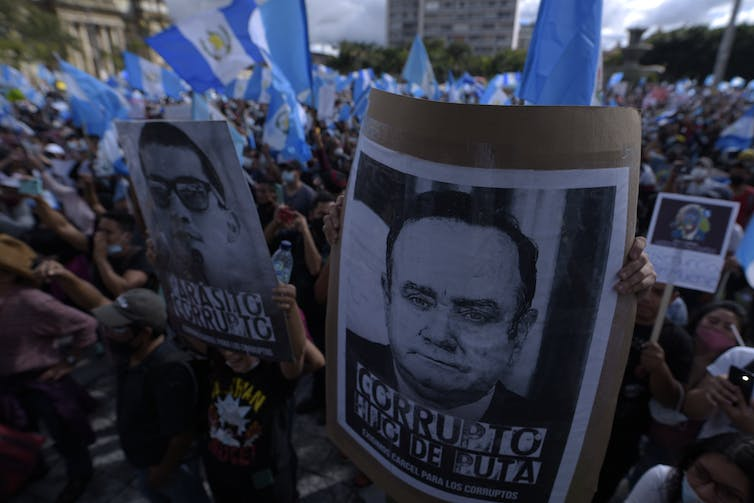 Protesters hold Guatemalan flags and posters alleging corruption fo the president