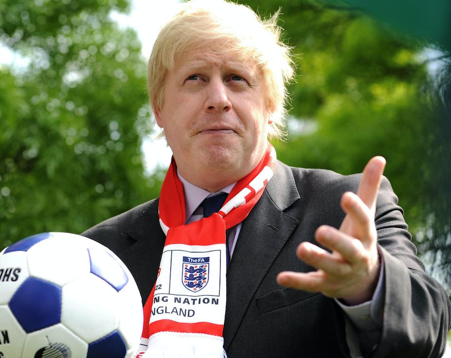 Boris Johnson holding a football wearing an England scarf