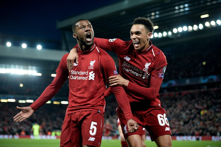 Liverpool's Georginio Wijnaldum celebrates on the pitch with his teammate Trent Alexander-Arnold.