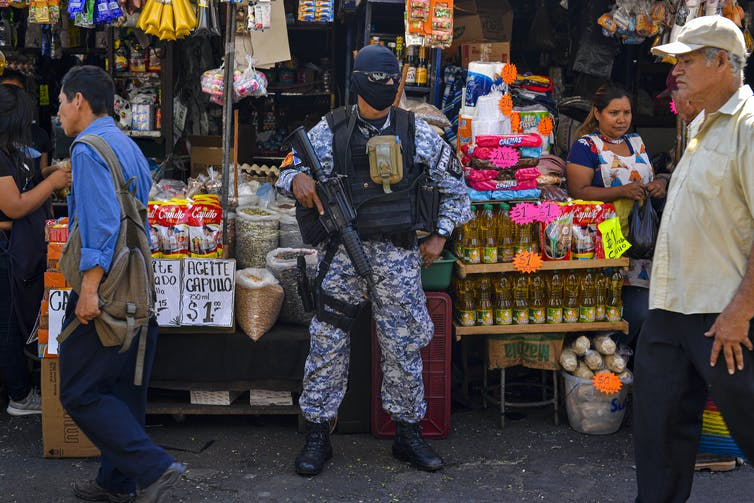 A police officer in full SWAT gear with a machine guns stands outside a small store on a city street as people walk by