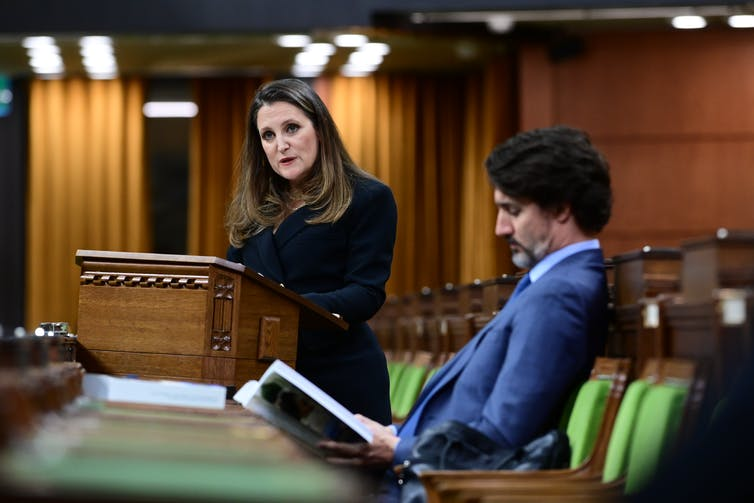 Chrystia Freeland stands at a podium to read the federal budget while Justin Trudeau leans back in his seat reading the budget document.