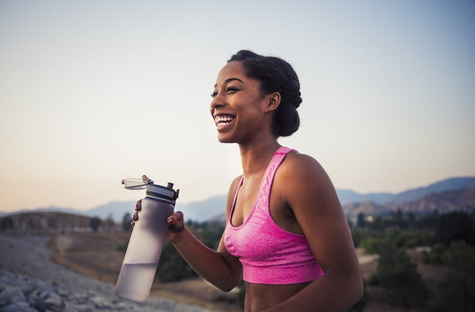 A woman outdoors holding a bottle of water.