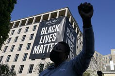 A man raises his fist in front of a Black Lives Matter banner.