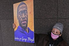 A woman in a pink mask holds up a poster of George Floyd.